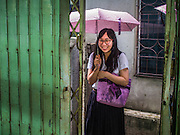 22 OCTOBER 2014 - BANGKOK, THAILAND: A Thai university student walks through the Ban Krua neighborhood in Bangkok during a rainstorm.      PHOTO BY JACK KURTZ