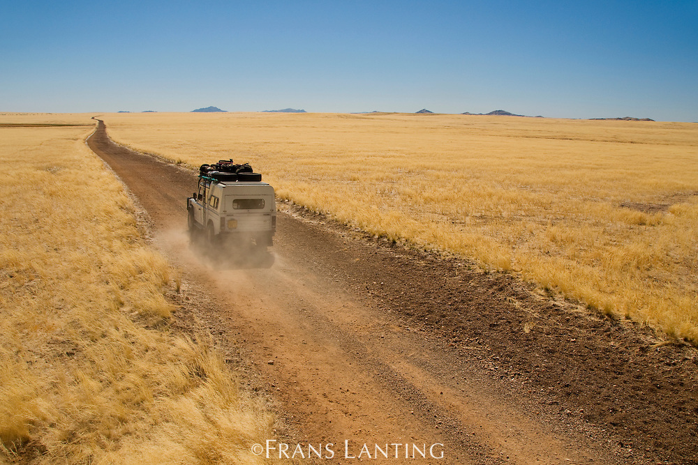 Safari vehicle on gravel park road, Namib-Naukluft National Park, Namibia