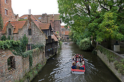 A canal boat full of tourists cruises by the B&B Bonifacius (left) in Bruges, Belgium. (Photo © Jock Fistick)