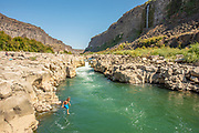 Kid jumping off cliff while swimming in the canyon on the Snake River near Twin Falls, Idaho.