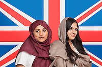 Portrait of two young Muslim women in traditional clothing standing against British flag