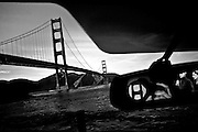 California's Golden Gate Bridge spans the San Francisco Bay as pedestrians and the photographer are reflected in a car's rear-view mirror.