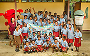 Lobo Village school kids show off a banner calling for conservation of Triton Bay, flanked by RARE Conservation Fellow Wida Sulistyaningrum and RARE mascots Red Snapper and Bryde's Whale.