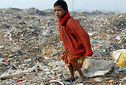 Boy watching an arriving dump truck at one of the largest landfills in New Delhi, India. Scavengers are environmentalists by necessity, reducing landfill mass by reselling plastic and rags.