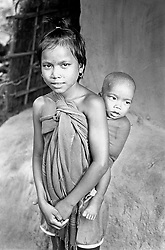BANGLADESH DINAJPUR DISTRICT KAHAROL THANA AUG94 - A girl carries her little sister in a cloth on her back in Dinajpur district...jre/Photo by Jiri Rezac..© Jiri Rezac 1994