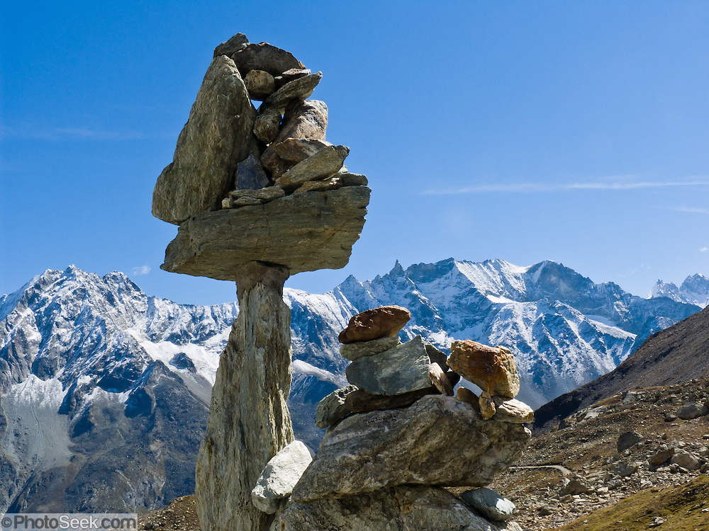 "A rock cairn balances above Arolla village (municipality of Evolène), in Val d'Hérens, Valais (Wallis or Valley) canton, Switzerland, on the High Route (Chamonix-Zermatt Haute Route), Europe. Snow dusts peaks of Les Dents des Veisivi (left) and Les Aiguilles de la Tsa (right) in the Pennine Alps. Published in ""Light Travel: Photography on the Go"" by Tom Dempsey 2009, 2010."