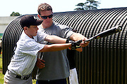 Nick Hundley helps a young baseball player during a training session with Major League Baseball pros Boston Red Sox pitcher Mark Melancon, San Diego Padres catcher Nick Hundley and Toronto Blue Jays infielder Chris Woodward at Lloyd Elsmore Park, Auckland. Wednesday 18 January 2011. Photo: Ella Brockelsby / photosport.co.nz