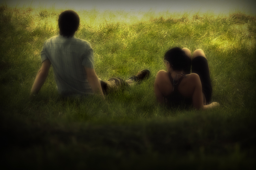 A young couple in a field of grass looking out toward the ocean, dreaming.