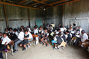 Learners from Grades 2 & 3 crowded in a shack with out desks...Mkanzini Junior Secondary School is one of 395 'mud schools' in the Eastern Cape where buildings are dilapidated and unsafe with insufficient desks and chairs. Facilities are lacking and there is no money for maintenance. Students learn under terrible conditions. Corrugated roofs leak when it rains, when its hot the heat becomes unbearable and when its cold it is too cold to write...Mkanzini is one of the schools seeking an order compelling the Basic Education Minister to prescribe minimum norms and standards for school infrastructure...Near Port St Johns. Eastern Cape...©Zute lightfoot / Legal Resources Centre