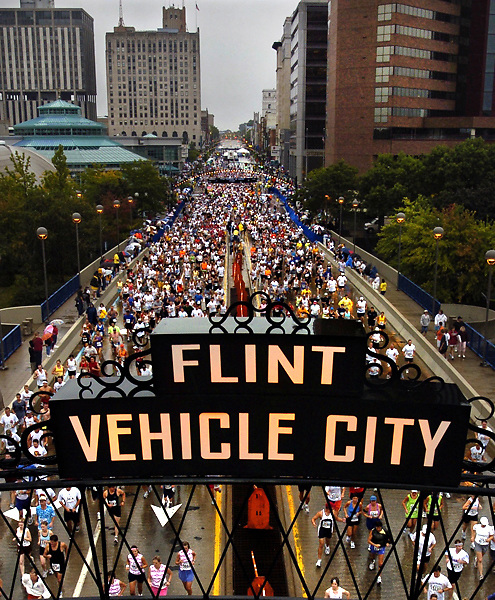 A record field of over 6,850 at the starting line for the 28th annual Crim 10-mile road race today in downtown Flint, Mich. The total for all nine events that make up the Crim Festival of Races was 13,347 at the close of Friday night registration. Weather delayed the start by 30 minutes. This was the first year the downtown's new arches - recreations of the metal spans that originally stood from 1899-1919.for the Crim that the arches spanned Saginaw St.  (Date shot: 8/28/04) (THE FLINT JOURNAL / STEVE JESSMORE)