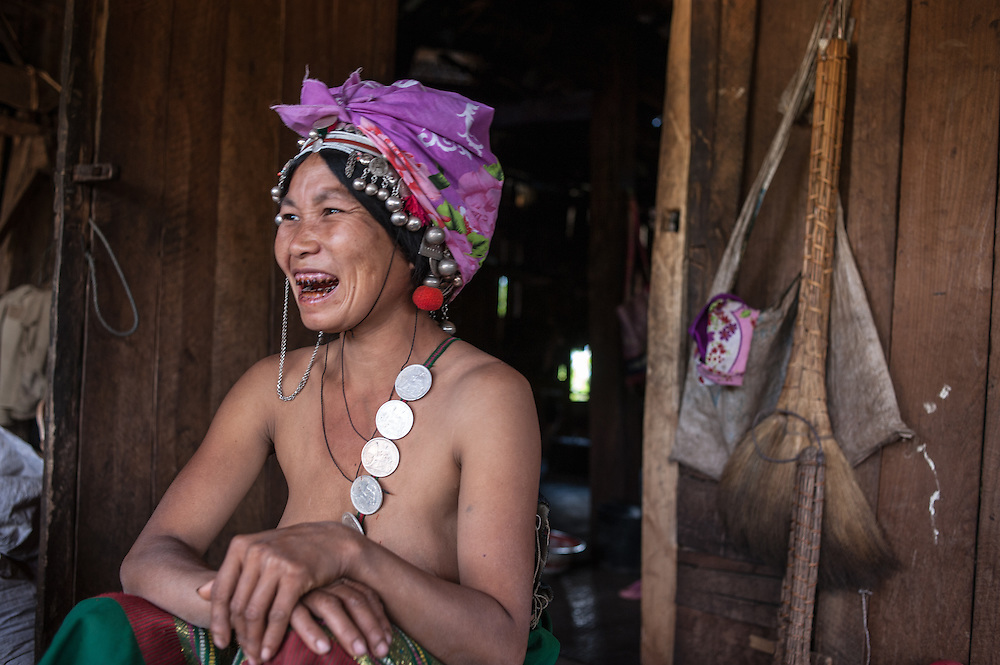 A hill tribe woman from Northern Laos laughs while talking with a photographer on the front porch of her village home