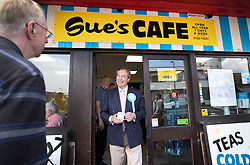 © Licensed to London News Pictures. 18/05/2019. Canvey Island, UK. Brexit Party leader Nigel Farage emerges from a cafe as he campaigns for the European Elections in Canvey Island in Essex. The European Elections are being held on Thursday 23rd May. Photo credit: Peter Macdiarmid/LNP