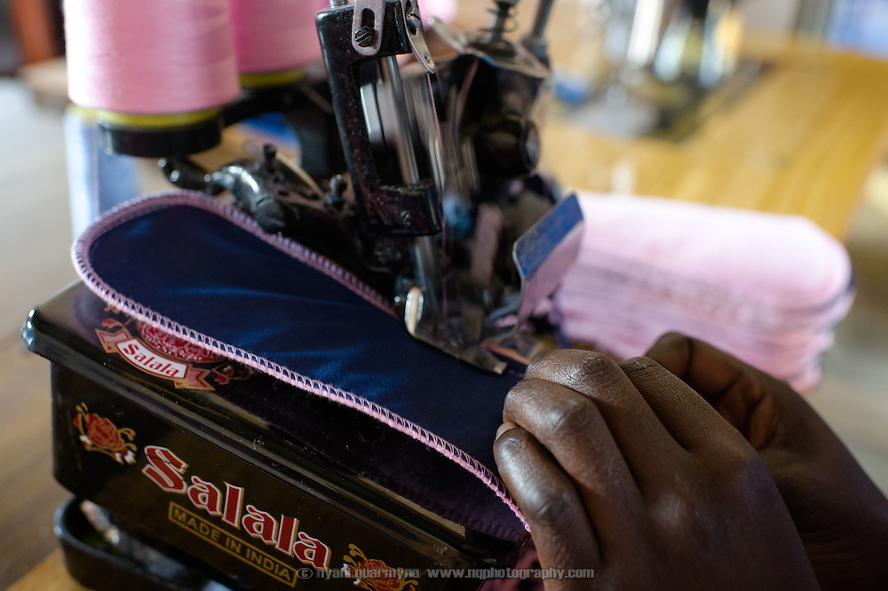 An Afripads employee sewing pads at the Afripads factory in the village of Kitengeesa in the Central Region of Uganda on 30 July 2014.<br /> <br /> Started by volunteers in 2009, Afripads manufactures reusable fibre sanitary pads made locally by community residents. Beginning with a single employee, the company now employs roughly 100 women and produces approximately 700 kits (consisting of pads, holders and a bag) each week. At USh 12,000 to 15,0000 (&pound;2.75 to &pound;3.40) for a kit that lasts approximately one year, Afripads offer a significant saving over disposables which may cost in excess of USh 42,000 (&pound;9.60) over the course of a year. And for the many girls and women who cannot afford disposables, they offer an affordable and more hygienic alternative to rags, cotton wool or toilet paper, all of which are frequently used. At schools where Afripads have been distributed, teachers report that absenteeism has dropped sharply as girls who previously did not have access to proper sanitary pads now no longer stay home when they have their periods.