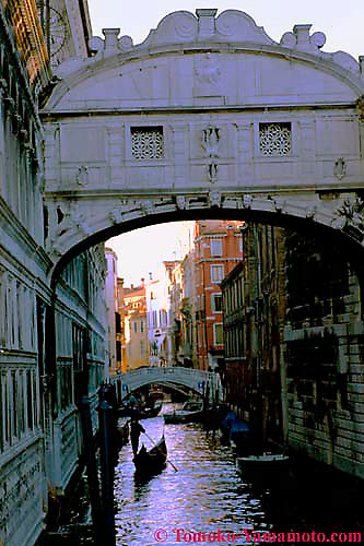 Gondolier and his gondola in silhouette moving away from Ponte dei Sospiri, the Bridge of Sighs.  The foreground, right under the bridge is dark, but bright light is on the building beyond a foot bridge over Rio del Palazzo. Photo of Venice, Italy by Tomoko Yamamoto.<br /> Foto der Seufzerbr&uuml;cke und des Gondoliere im Schattenriss in Venedig, Italien. Venezia, Italia.