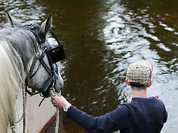 © Licensed to London News Pictures. <br /> 05/06/2014. <br /> <br /> Appleby, Cumbria, England<br /> <br /> A young boy prepares to take his horse into the River Eden as gypsies and travellers gather during the annual horse fair on 5 June, 2014 in Appleby, Cumbria. The event remains one of the largest and oldest events in Europe and gives the opportunity for travelling communities to meet friends, celebrate their music, folklore and to buy and sell horses.<br /> <br /> The event has existed under the protection of a charter granted by King James II in 1685 and it remains the most important event in the gypsy and traveller calendar.<br /> <br /> Photo credit : Ian Forsyth/LNP