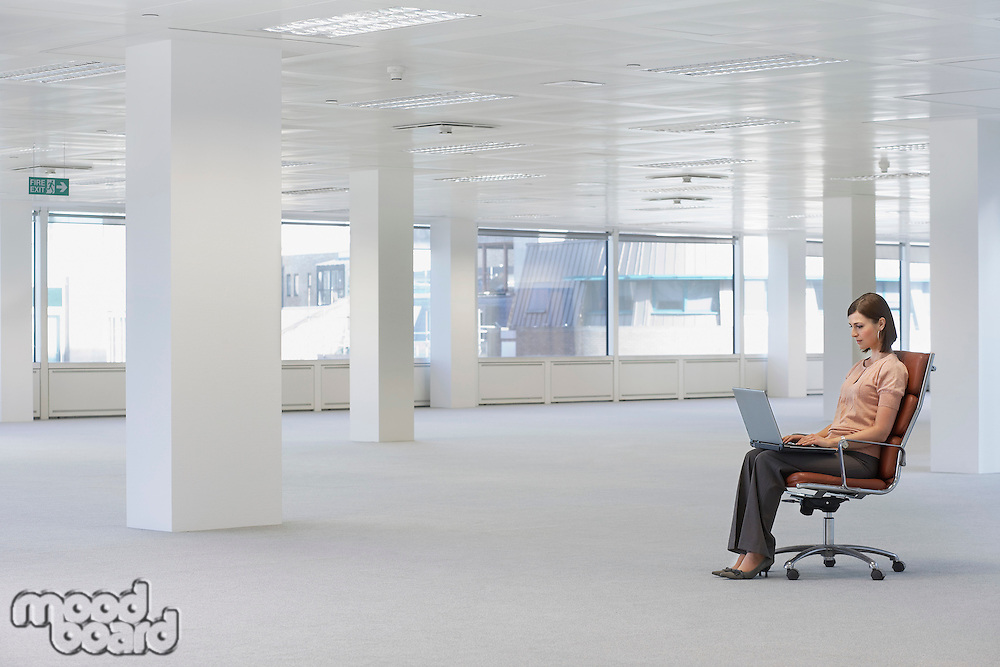 Young woman sitting in swivel chair using laptop in empty office space side view