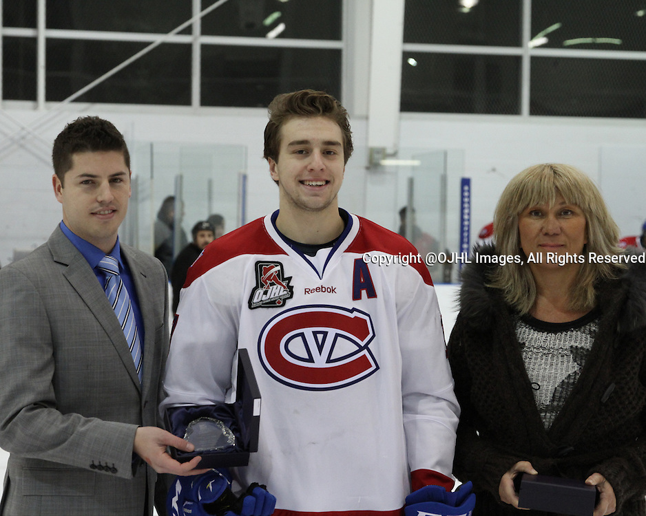 KINGSTON, ON - Dec 3, 2015 : Ontario Junior Hockey League game action between the Pickering Panthers and the Kingston Voyageurs. Anthony Rinaldi #17 of the Kingston Voyageurs accepts his player of the month award for October from OJHL executive Brett Garbutt (left) and Voyageurs govenor Dr. Dijana Oliver (right) during a special presentation made prior to the game. <br /> (Photo by Robert John Boucher / OJHL Images)
