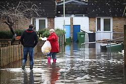 © Licensed to London News Pictures. 25/02/2014. Basingstoke, Hampshire, UK. Evacuated residents making their way through flood water to collect more of their possessions on Grampian Way in the Buckskin area of Basingstoke, Hampshire. Groundwater levels are continuing to rise slowly in the area, where many homes have been evacuated. Water is still being pumped by tankers, and taken to nearby sewerage plants. Photo credit : Rob Arnold/LNP