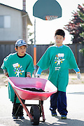Howard Chang, 9, left, and Nathan Wang, 10, roll a wheelbarrow of soil across the schoolyard during Comcast Cares Day at Curtner Elementary School in Milpitas, California, on April 27, 2013. (Stan Olszewski/SOSKIphoto)