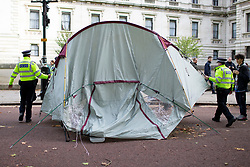 © Licensed to London News Pictures. 09/10/2019. London, UK. Police remove tents from an Extinction Rebellion roadblock on Horse Guards Road. Police continue to attempt to clear roads in Westminster on the third day of the protest.  Photo credit: George Cracknell Wright/LNP