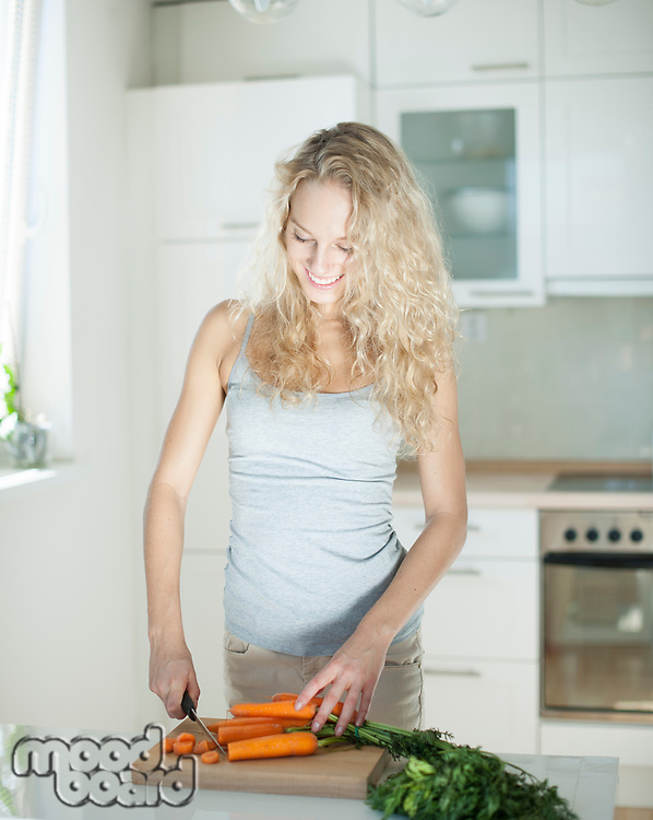 Happy young woman chopping carrots on board in kitchen