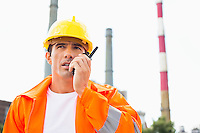 Male construction worker wearing reflective workwear communicating on walkie-talkie at site
