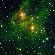 Two bright stars illuminate a greenish mist in this and other images from the new 'GLIMPSE360' survey from NASA's Spitzer Space Telescope. This fog is comprised of hydrogen and carbon compounds called polycyclic aromatic hydrocarbons (PAHs), which are found right here on Earth in sooty vehicle exhaust and on charred grills. In space, PAHs form in the dark clouds that give rise to stars. These molecules provide astronomers a way to visualize the peripheries of gas clouds and study their structures in great detail. They are not actually 'green;' but are colour coded in these images to let scientists see their glow in infrared. This image is a combination of data from Spitzer and the Two-Micron All-Sky Survey (2MASS). 2009