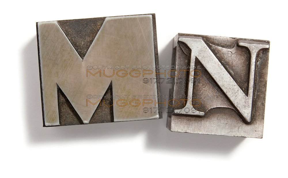 Letterpress M and N print blocks on white background