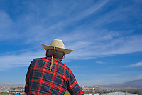 A man in a sombrero or cowboy hat crosses a bridge on a sunny day in Leon, Mexico near San Miguel de Allende.