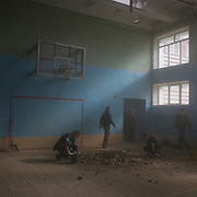 Local volunteers clean a school gymnasium damaged by shell-fire in Donetsk