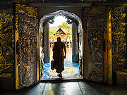 "03 APRIL 2016 - CHIANG MAI, THAILAND: A Buddhist monk leaves the ordination hall of Wat Sri Suphan. Wat Sri Suphan is also known as the ""Silver Temple"" because of its silver ubosot, or ordination hall. The temple is more than 500 years old but the silver ordination hall was recently remodeled. The ordination hall is covered in silver and the interior is completely done in silver and gold. It's traditionally served as the main temple for the silversmiths of Chiang Mai, whose community is around the temple.      PHOTO BY JACK KURTZ"