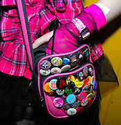 Detail of girl's magenta dress and gloves, with pink handbag covered in badges, CSS gig, February 2007