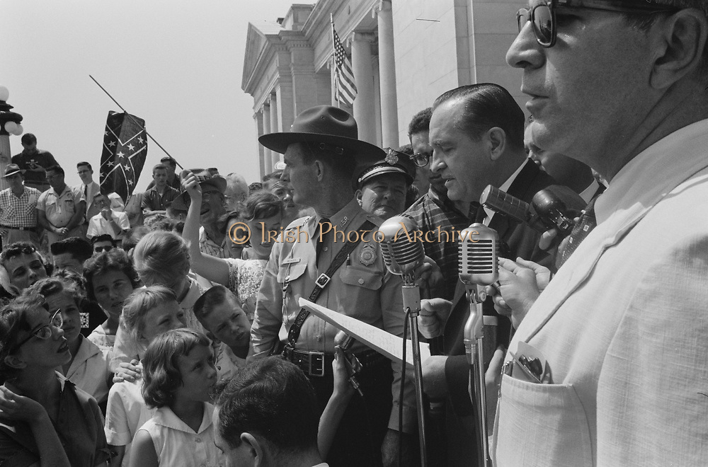 Little Rock, USA, 1959. Rally at state capitol.  Photograph shows a group of people, one holding a Confederate flag, surrounding speakers and National Guard, protesting the admission of the 'Little Rock Nine' to Central High School. 20 August 1959. Photographer: John T  Bledsoe.