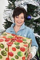 Senior woman holding present by Christmas tree
