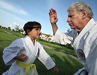 Karate coach Vicente Gonzalez, right, fights with Dylan Aleman, 5, during his training session at Sunset Lake Community Center on Monday July 6, 2009. Staff photo/Cristobal Herrera..