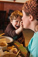 A toddler putting food into his Mothers mouth and laughing.