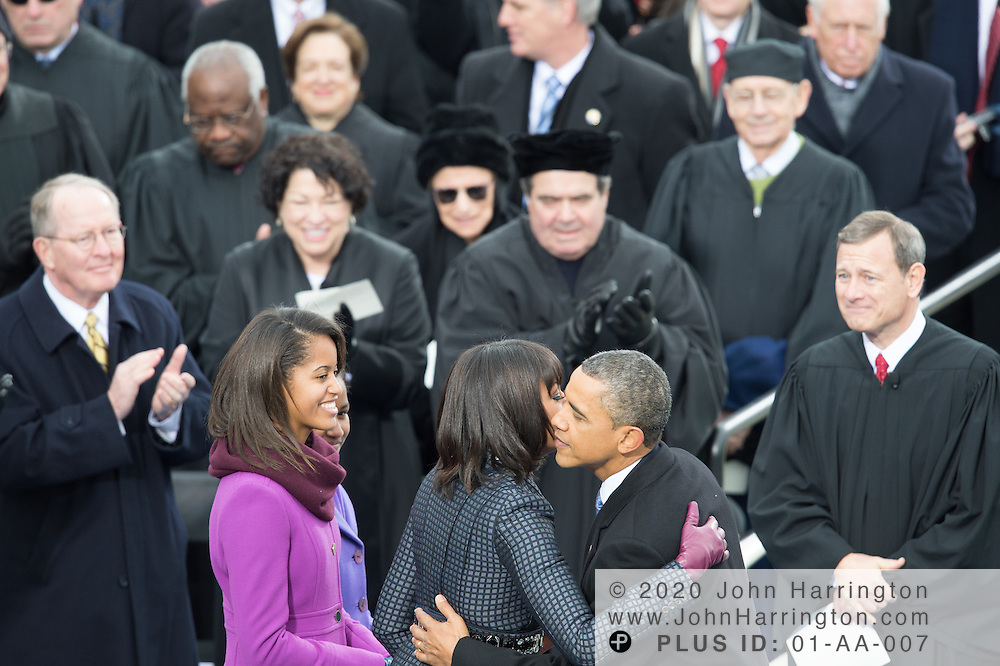 As Supreme Court justices applaud and look on, Michelle Obama congratulates her husband after he is sworn in for a second term during the 57th Presidential Inauguration of President Barack Obama at the U.S. Capitol Building in Washington, DC January 21, 2013.