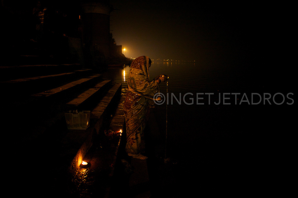 A woman is performing rituals while praying, very early morning at the Holy River Ganges.<br />