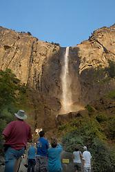Tourists gaze at Bridalveil Fall, Yosemite National Park, California, USA.