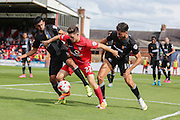 Mansfield Town defender Malvind Benning and Mansfield Town defender Ryan Tafazolli try to disposes York City forward Reece Thompson  during the Sky Bet League 2 match between York City and Mansfield Town at Bootham Crescent, York, England on 29 August 2015. Photo by Simon Davies.