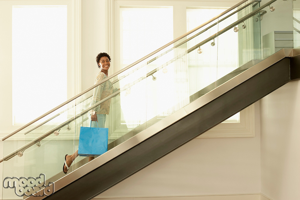 Young woman walking up the modern stairs with shopping bag portrait