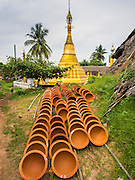 02 NOVEMBER 2014 - TWANTE, YANGON DIVISION, MYANMAR: Pottery bowls dry in front of a pagoda in Twante, Myanmar. Twante, about 20 miles from Yangon, is best known for its traditional pottery. The pottery makers are struggling to keep workers in their sheds though. As Myanmar opens up to outside investments and its economy expands, young people are moving to Yangon to take jobs in the better paying tourist industry or in the factories that are springing up around Yangon.    PHOTO BY JACK KURTZ