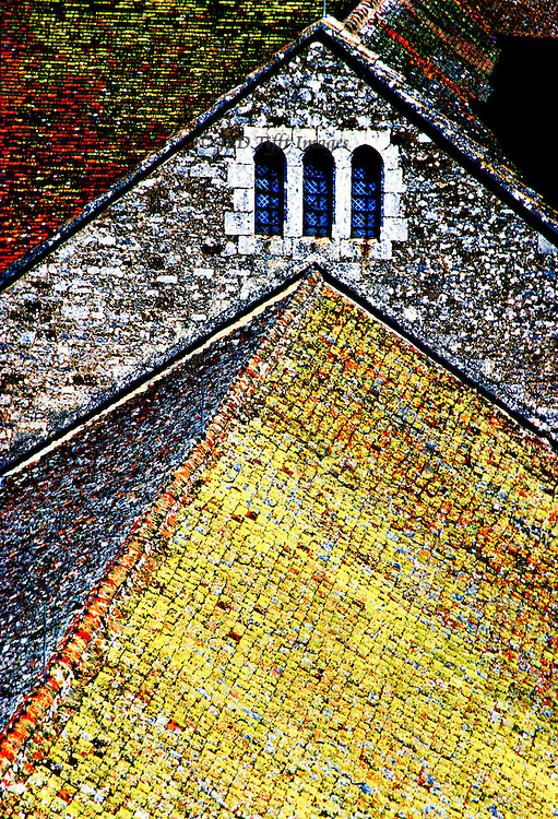 Angular abstract design formed by the rooftop of Vezelay Abbey, seen from the top of the bell tower.  Thick mosses cover and color the roof tiles.