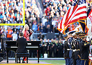 An American flag and other flags wave in the wind as Lady Gaga sings the National Anthem with a piano player assisting her before the Denver Broncos NFL Super Bowl 50 football game against the Carolina Panthers on Sunday, Feb. 7, 2016 in Santa Clara, Calif. The Broncos won the game 24-10. (©Paul Anthony Spinelli)