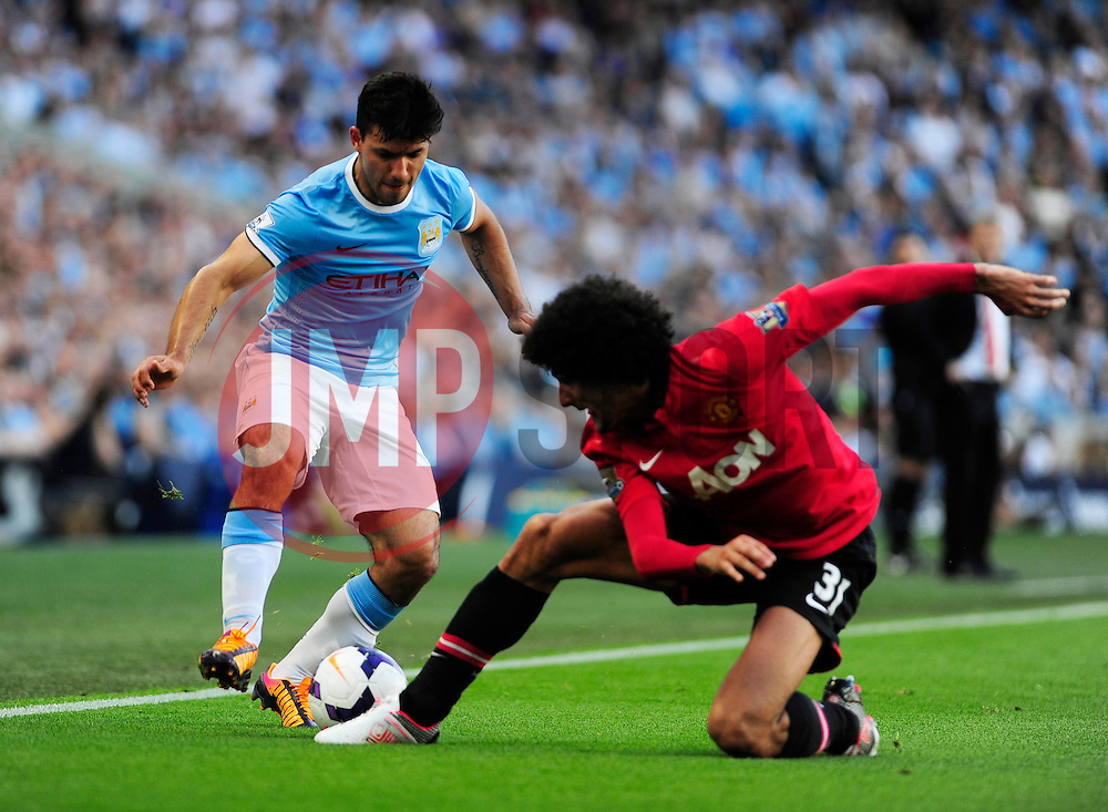 Manchester City's Sergio Aguero is challenged by Manchester United's Marouane Fellaini - Photo mandatory by-line: Dougie Allward/JMP - Tel: Mobile: 07966 386802 22/09/2013 - SPORT - FOOTBALL - City of Manchester Stadium - Manchester - Manchester City V Manchester United - Barclays Premier League
