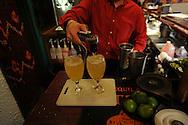 A restaurant worker prepares margaritas.