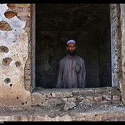 An Afghanistan man looks out from what is left of his home in the Shomali Valley of Afghanistan.  It was destroyed by the Taliban.