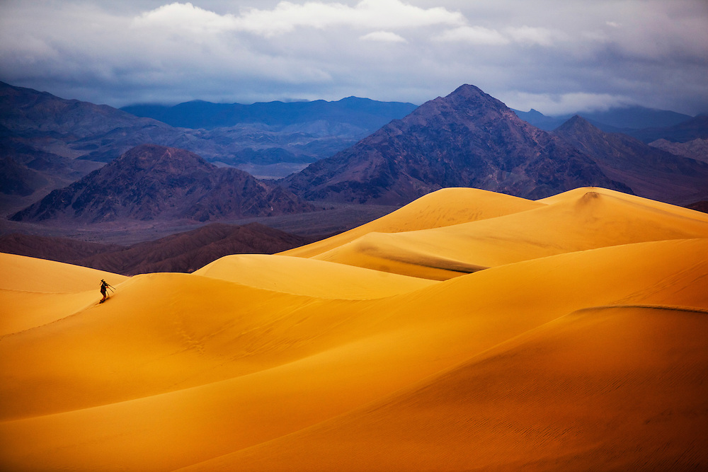 A visitor to Death Valley National Park climbs towering dunes against a backdrop of blue and purple hued mountains.
