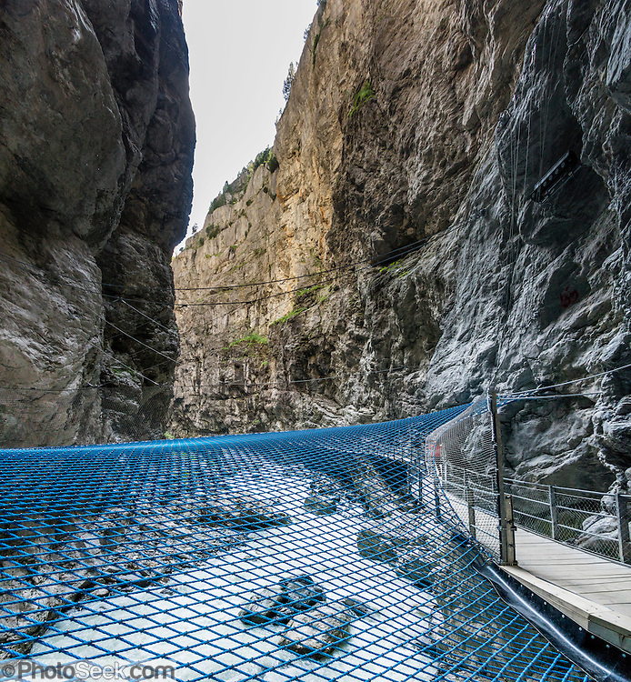 Walk across a blue net suspended over the White Lütschine river gorge, in the Gletscherschlucht of Grindelwald, Switzerland, Europe. Walk boardwalks and tunnels through the dramatic Gletscherschlucht, a deep gorge of the White Lütschine river, flowing from Lower Grindelwald Glacier. From Gletscherschlucht hotel restaurant in Grindelwald, a wooden walkway leads over raging water, through galleries and rocky tunnels over 1000 meters into the ravine, under 100-meter high cliffs. Visitors can amble on a blue net over the foaming torrent. Walk there in 35 minutes from the center of Grindelwald, or take the bus. The tongue of Lower Grindelwald Glacier last extended through Gletscherschlucht gorge in 1855 and has receded very rapidly, melting back more than 3.75 kilometers as of 2014. Consistent with a pattern global warming, the glacier may entirely disappear by 2100. This image was stitched from multiple overlapping photos.