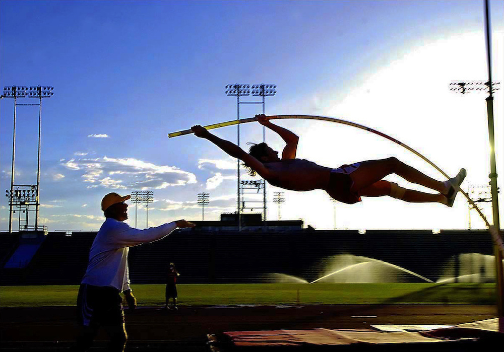 Xavier Mascareñas/New Mexico Daily Lobo; University of New Mexico pole vaulter Derek Mackel gets a spot from assistant track and field coach Scott Steffan during practice June 4, 2006, at the Great Friends of UNM Track and Field Stadium.